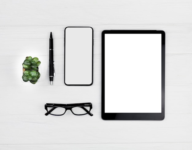 Vista superior disposición de papelería sobre fondo azul con tableta y teléfono maqueta