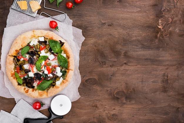 Vista superior disposición de pizza y cortador