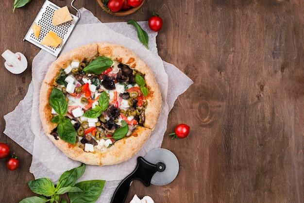 Vista superior de la disposición de pizza y cortador