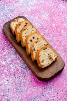 Vista superior distante delicioso pastel de pasas tarta en rodajas sobre la superficie rosa pastel hornear azúcar dulce color de galleta