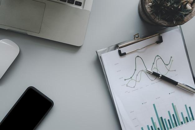 Vista superior de documentos comerciales, gráficos y tablas, y computadoras, cuadernos y bolígrafos.concepto de negocios y finanzas