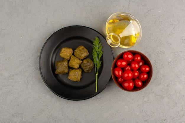 Vista superior de dolma dentro de la placa negra junto con aceite de oliva y tomates cherry rojos sobre el gris