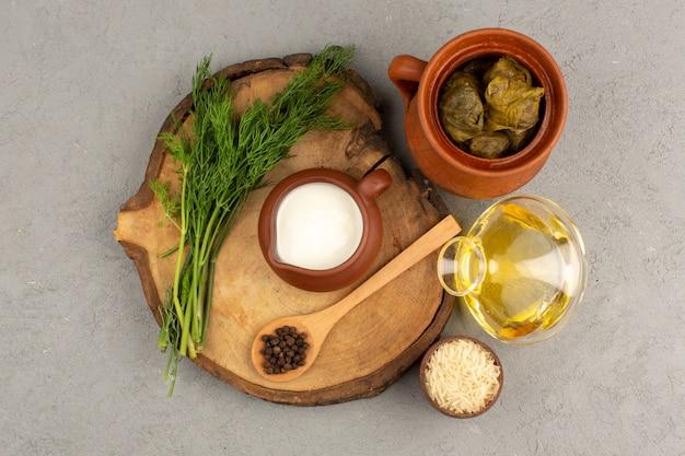 Vista superior dolma green junto con yogurt y aceite de oliva en el gris