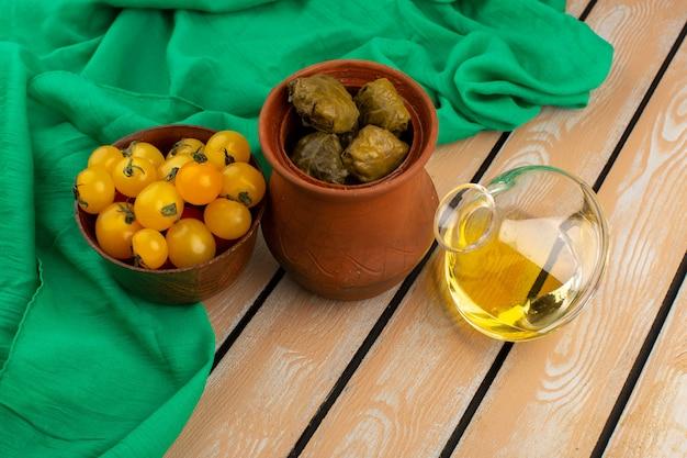Vista superior dolma junto con tomates amarillos y aceite de oliva en el tejido verde y madera rústica