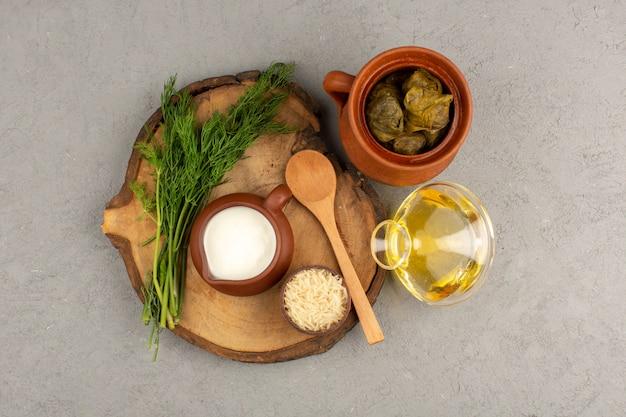 Vista superior de dolma verde con carne picada en el interior junto con yogur y aceite de oliva en el gris