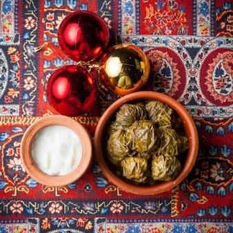 Vista superior de dolma con yogur y bolas de navidad en un plato de arcilla en la alfombra