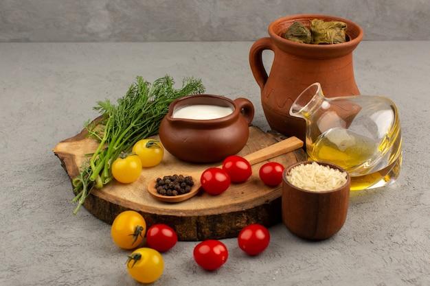 Vista superior de dolma con yogurt aceite de oliva y tomates en el gris
