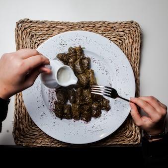 Vista superior dolma con yogurt y tenedor y mano humana en servilletas