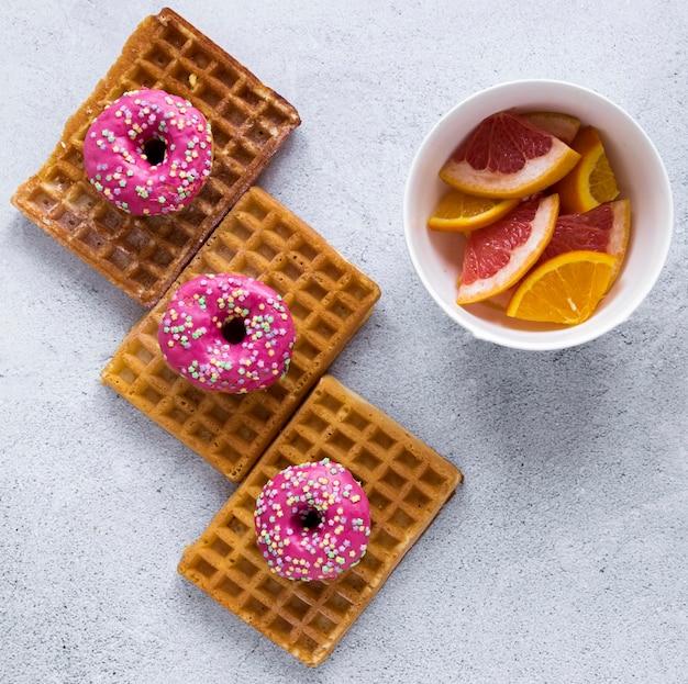 Vista superior de donas en waffles con cítricos