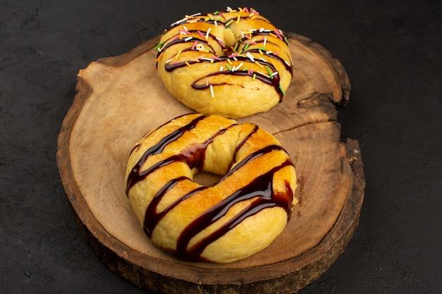 Vista superior donuts delicioso delicioso con chocolate en el escritorio marrón y fondo gris