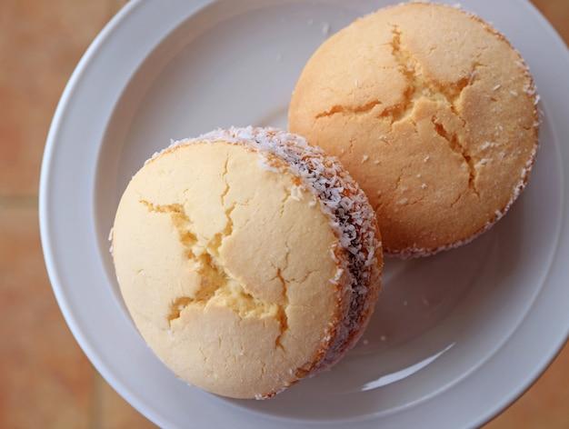 Vista superior de dos alfajores, dulces latinoamericanos tradicionales servidos en un plato blanco