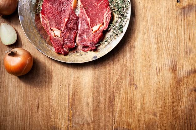 Vista superior de dos carnes crudas frescas sazonadas con sal, pimienta y romero en plato vintage junto a cebolla blanca picada. proteína saludable.