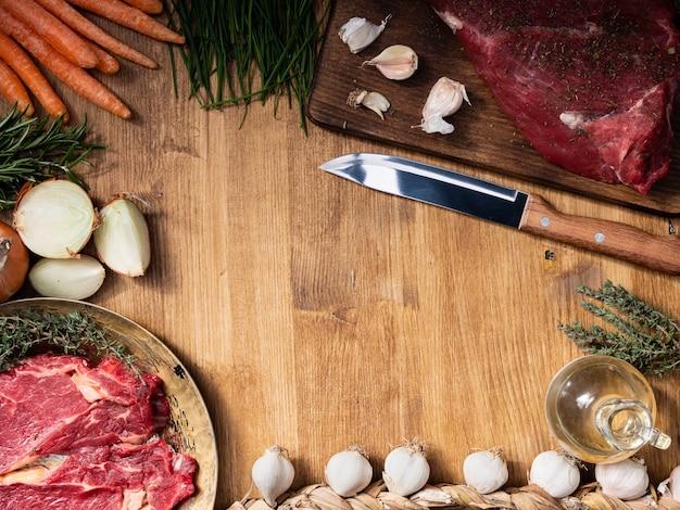 Vista superior de dos carnes rojas diferentes al lado de verduras frescas con espacio de copia libre en el centro del marco. mesa de madera. . cebolla rebanada. hierbas verdes.