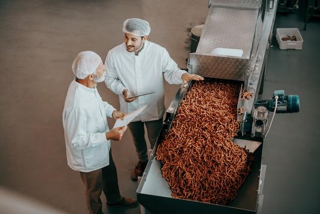 Vista superior de dos controladores de calidad caucásicos de pie junto a la máquina con palos salados y evaluando la calidad. ambos están vestidos con uniformes blancos y con redecillas para el cabello. interior de la planta de alimentos.