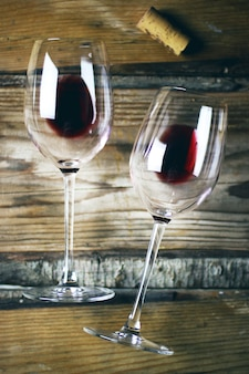 Vista superior de dos copas de vino tinto y plato de queso