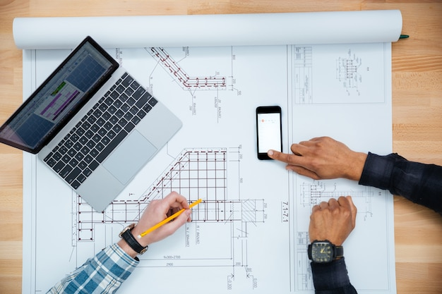 Vista superior de dos hombres que trabajan para planos mediante teléfono móvil y computadora portátil