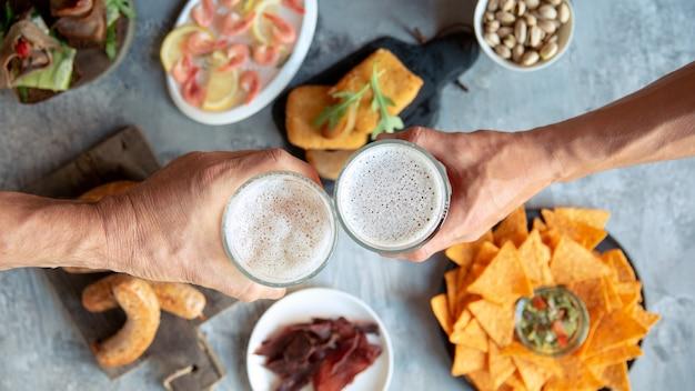 Vista superior de dos manos con vasos de cerveza y deliciosos bocadillos.
