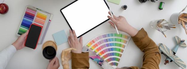 Vista superior de dos mujeres diseñadoras trabajando juntas en un espacio de trabajo mínimo con tabletas, teléfonos inteligentes y suministros de diseño.
