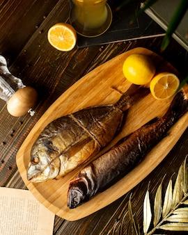 Vista superior de dos pescados ahumados colocados en un plato de bambú con mitades de limón