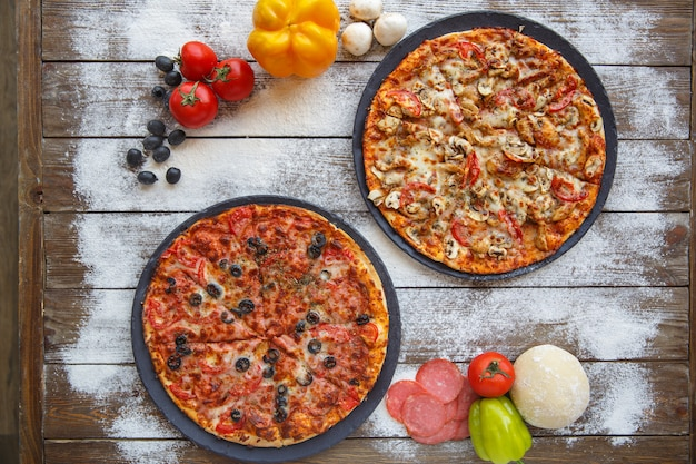 Vista superior de dos pizzas italianas en fondo de madera con espolvoreados de harina