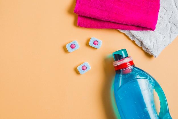 Vista superior de dos toallas y detergente líquido con pastillas para lavavajillas.