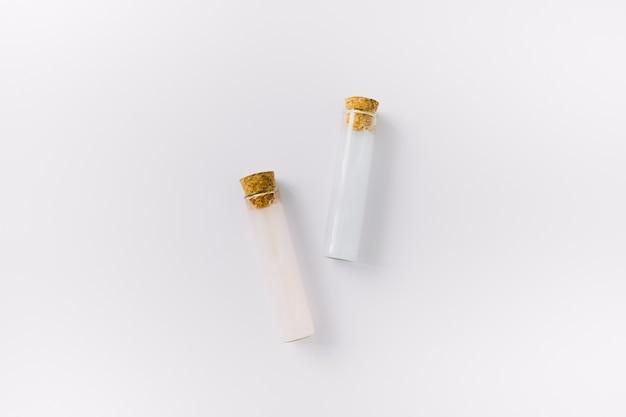 Vista superior de dos tubos de ensayo de aceite esencial en superficie blanca