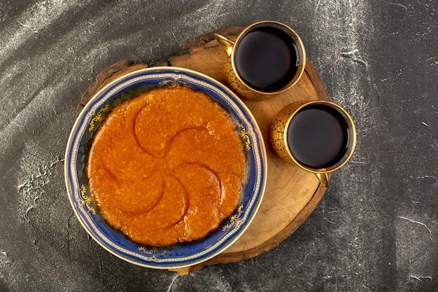 Una vista superior dulce delicioso halva delicioso postre dulce oriental dentro de la placa con té