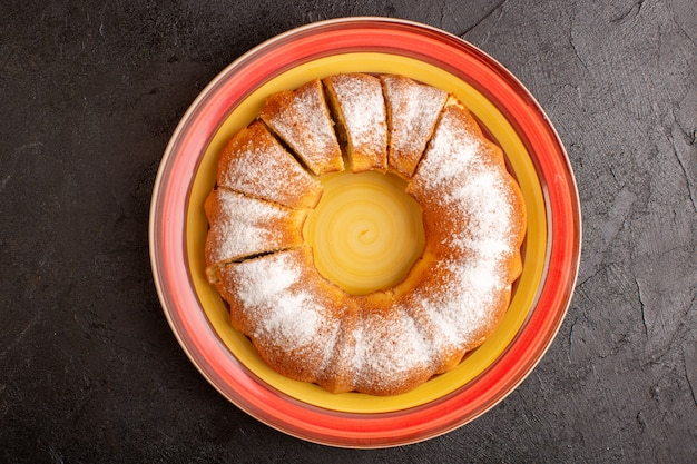 Una vista superior dulce pastel redondo con polvo de azúcar en rodajas dulce delicioso pastel aislado dentro de la placa y fondo gris galleta galleta de azúcar