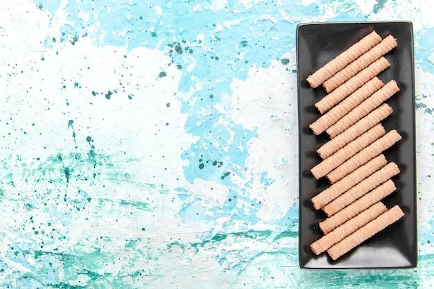 Vista superior dulces galletas largas dentro de un molde para pastel negro sobre el fondo azul claro