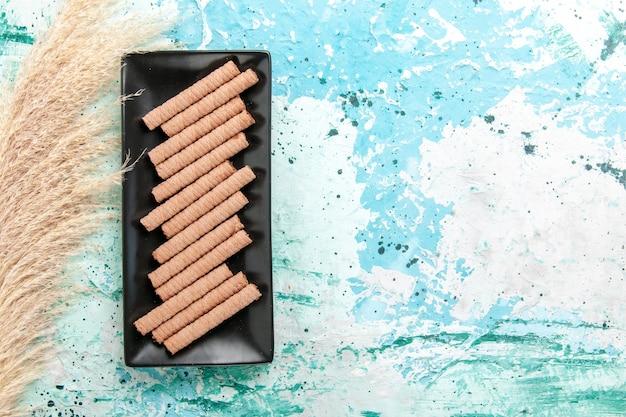 Vista superior dulces galletas largas dentro de molde para pastel negro sobre fondo azul.