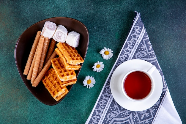 Vista superior dulces gofres panecillos dulces y mermelada con una taza de té en verde