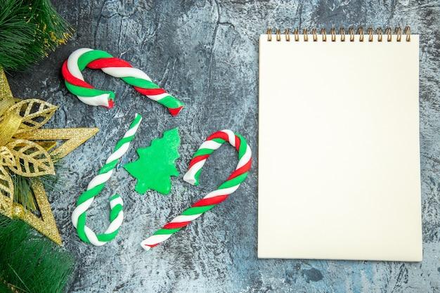 Vista superior de dulces de navidad adornos de navidad un cuaderno sobre una superficie gris