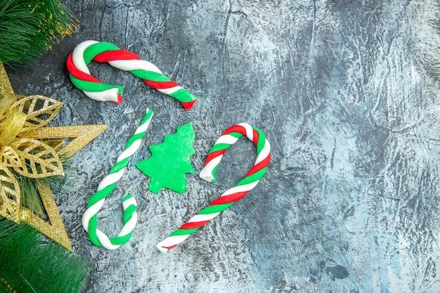 Vista superior de dulces de navidad adornos de navidad sobre fondo gris