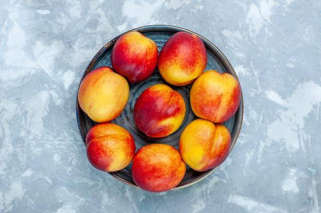 Vista superior de duraznos frescos deliciosas frutas de verano en el escritorio blanco claro