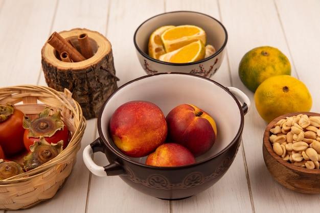 Vista superior de duraznos frescos en un recipiente con caquis en un balde con maní en un recipiente de madera sobre un fondo blanco de madera