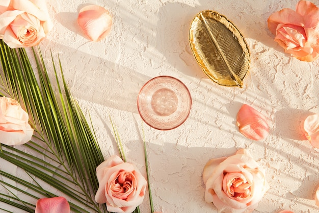 Vista superior de la elegante composición con flores de rosas de peonía rosa, hojas de palmeras tropicales, placa dorada y vidrio sobre textura pastel