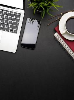 Vista superior del elegante espacio de trabajo con computadora portátil, teléfono inteligente, taza de café, computadora portátil, espacio de copia