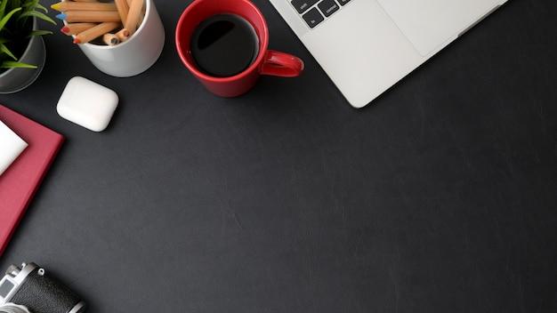 Vista superior del elegante espacio de trabajo con laptop, taza de café y espacio de copia