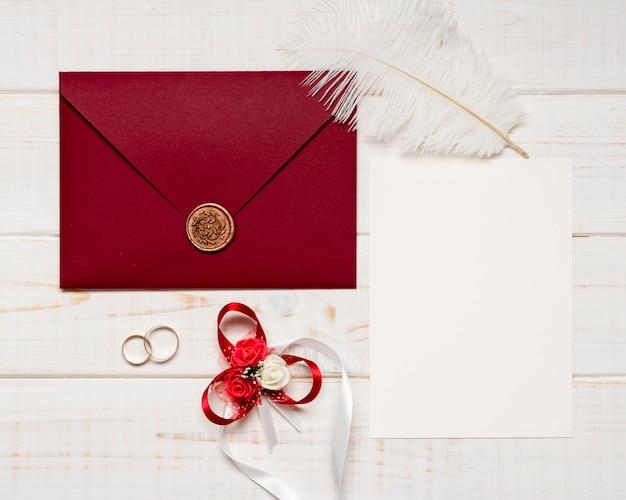 Vista superior elegante invitación de boda con anillos de compromiso