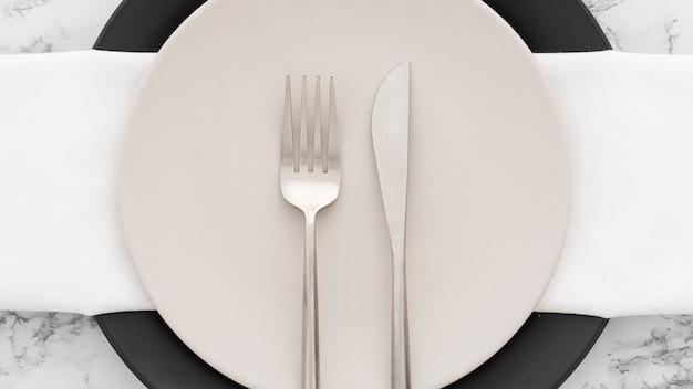 Vista superior elegante plato con cubiertos en la parte superior