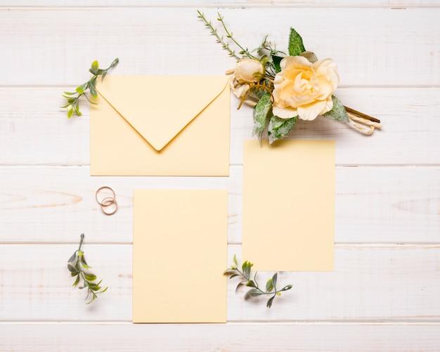 Vista superior elegantes sobres con flores de boda