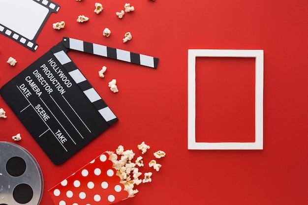 Vista superior de elementos de cine sobre fondo rojo con marco blanco