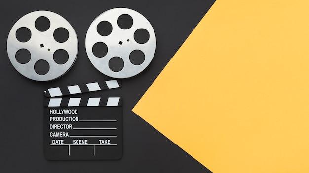 Vista superior de elementos de creación de películas sobre fondo bicolor con espacio de copia