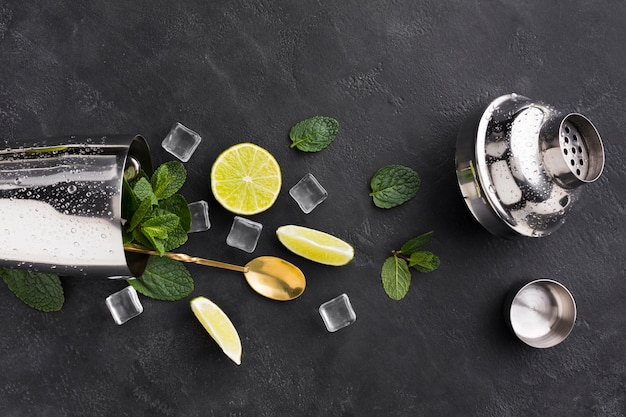 Vista superior de elementos esenciales de cóctel con agitador y cubitos de hielo.