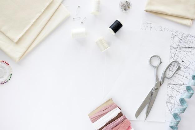 Vista superior de elementos esenciales de costura con textiles y tijeras.