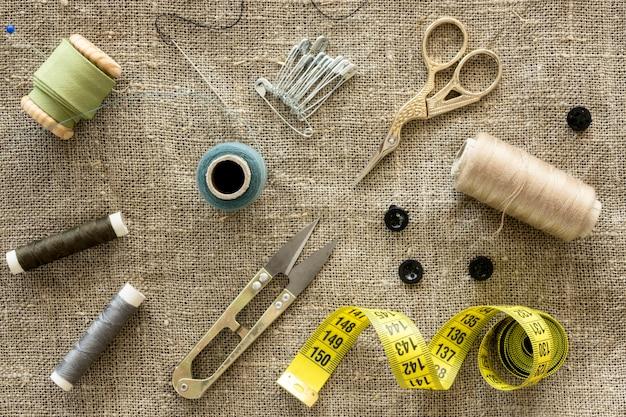 Vista superior de elementos esenciales de costura con tijeras e hilo