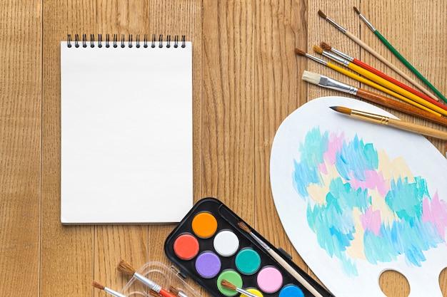 Vista superior de los elementos esenciales de pintura con cuaderno y paleta.