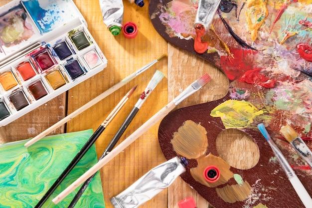 Vista superior de elementos esenciales de pintura con paletas y pinceles.