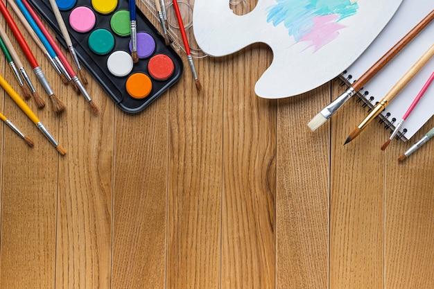 Vista superior de los elementos esenciales de pintura con pinceles y paleta.