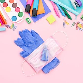 Vista superior de los elementos esenciales de regreso a la escuela con guantes y mascarilla médica.
